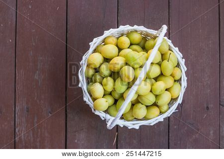 Ripe Juicy Colorful Yellow And Green Plums In A Wicker Basket. Dark Concrete Stone Background.