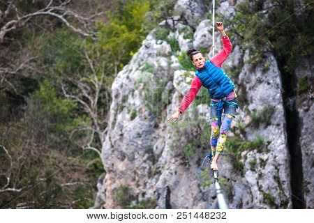 Highliner On A Rope. Highline On A Background Of Mountains. Extreme Sport On The Nature. Balancing O