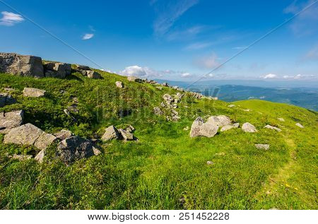 Grassy Meadow On Hillside. Huge Rocky Formation. Beautiful Summer Scenery In Wonderful Weather.