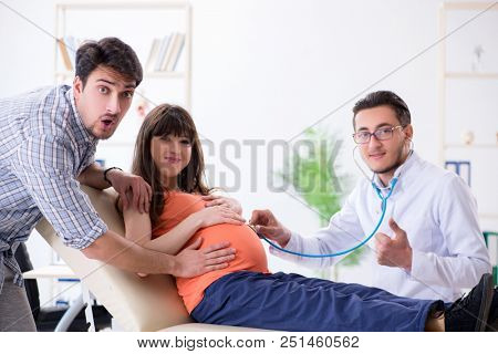 Pregnant woman with her husband visiting the doctor in clinic