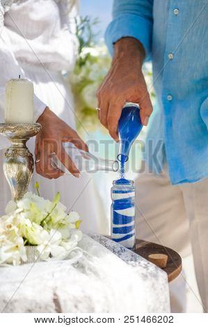 Close Up Of A Wedding Couple Hand Mixing White And Blue Sand Ceremonies, The Groom And The Bride Pou