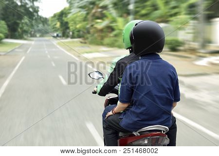 Portrait Of Motorcycle Taxi Driver Delivering The Passenger To His Destination On The City