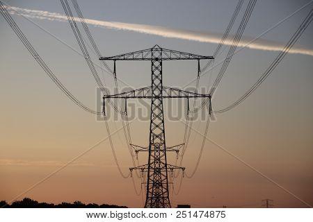 Sunset Over The Eendragtspolder In Zevenhuizen, The Netherlands With Silhouette Of Powerlines And Tr
