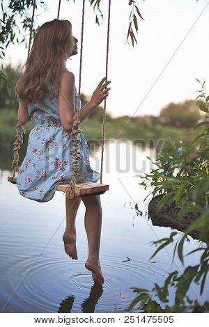 Young Sexy Woman Swinging On The Swing Outdoor Above The Lake. Beautiful Legs Without Hair, Hair Fre