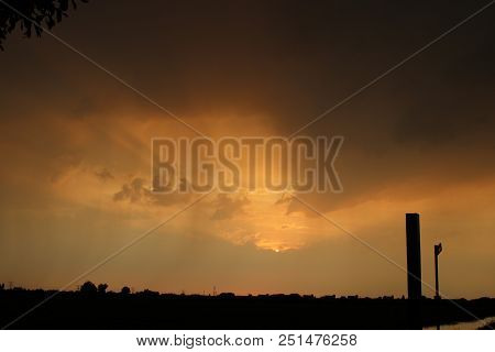 Colorful Sunset With Sun Beams From Behind The Clouds Reflecting With Coming Thunderstorm