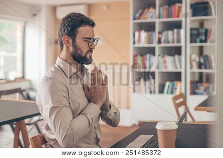 Meditating young man in coworking