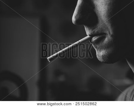 A Guy With A Cigarette In His Mouth. Closeup.