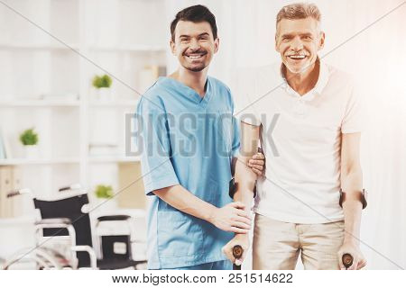 Smiling Doctor Helps Old Man Patient With Crutches. Care For Elderly People Concept. Concept Of Heal