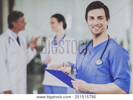 Male Doctor With Stethoscope In Blue Uniform. Work In Hospital. Concept Of Health Care. Medical Cons