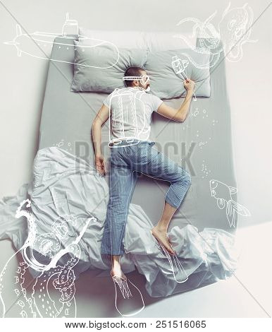 Top View Photo Of Young Man Sleeping In A Big White Bed. Dreams Concept. He Is Dreaming About Underw