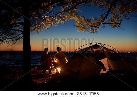 Night Camping At Lake. Tourist Tent And Back View Of Young Couple, Boy And Girl At Campfire Under Tr