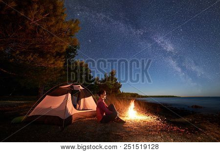 Night Camping On Sea Shore. Smiling Woman Hiker Sitting Relaxed In Front Of Tourist Tent At Campfire
