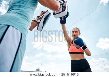 Low Angle Of Motivated Young Girl Boxing With Male In Open Air. She Is Throwing Jab Punch At Guy Whi