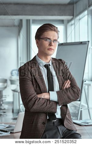 Young Businessman Wearing Eyeglasses At Office Leaning On Table Crossed Arms Looking Out The Window