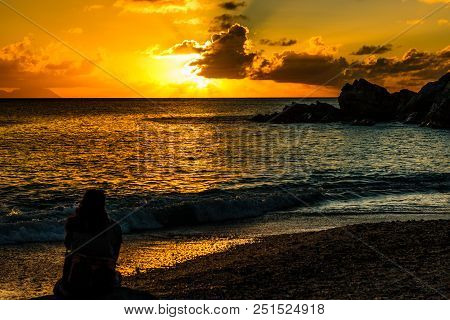 Travel Photo In St. Barths, Caribbean. View Of A Tourist Looking At Amazing Sunset On Shell Beach In