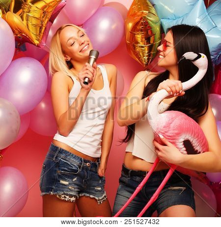 lifestyle, party  and people concept: Happy young girls with microphone and flamingo over ?ackground of  colorful balloons