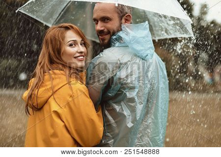 Happy Couple Walking Under Umbrella Hiding From Rain. They Are Turning In Delight Enjoying Leisure T
