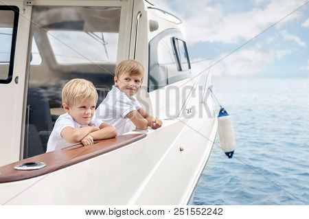 Two Cute Caucasian Blond Boys On Board Of White Luxury Yacht On Bright Summer Day. Siblings Having F