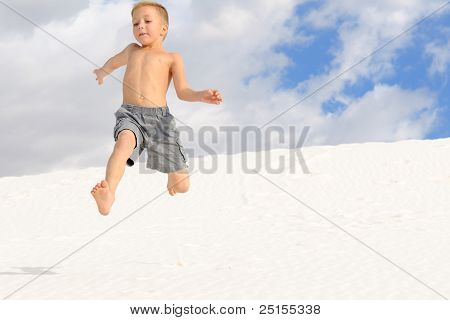 Young Boy Leaping Down a Sand Dune