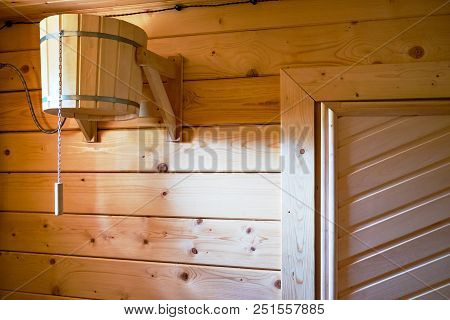 Interior Of A Small Wooden Sauna In A Spa. Focus On Wooden Bucket With Cold Water