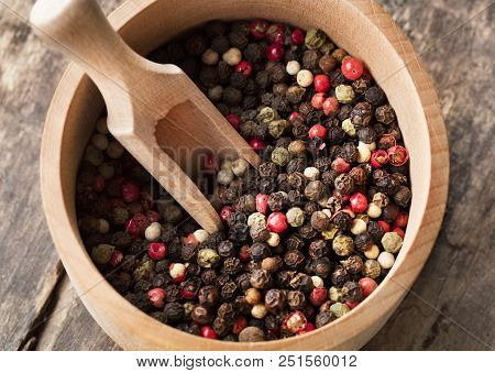Mixed Colored Peppercorn With Wooden Scoop On Wooden Background