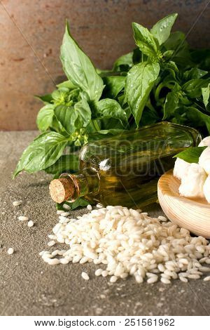 Small Balls Of Mozzarella Cheese With Basil Leaves, Rice Arborio And Olive Oil On Rustic Background