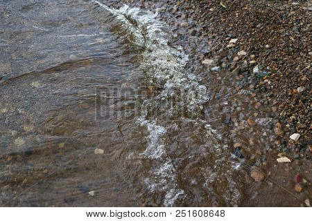Sea Pebbles And Waves. Clear Water Near The Shore With Pebbles At The Bottom. Sea Waves Crashing On