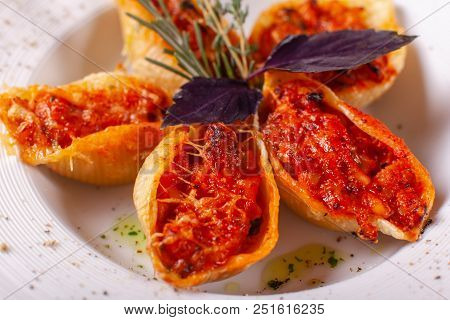 Italian Pasta Conchiglioni Rigati Stuffed With Dry Tomatoes And Meat. Sprinkled With Cheese.
