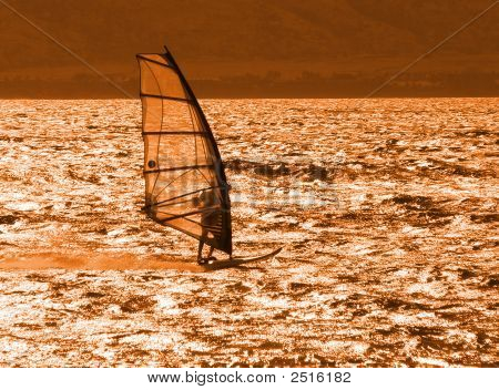 Young Windsurfer Alone At Sunset
