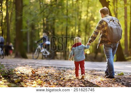 Father And His Little Son During The Hiking Activities In Forest At Sunset. Family Walking In Autumn