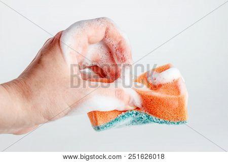 Hand grasps sponge for washing dishes on white background poster
