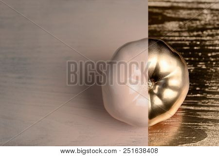 Gold And Beige Or Ecru Half Painted Tomato On Golden And Wooden Background