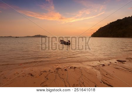 Wooden Boat On A Beach At Sunset.