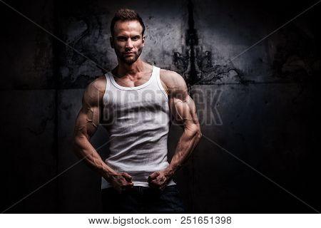 Studio Shot Of Strong Athletic Man In White Tshirt On Dark Grunge Background