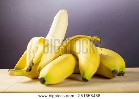 Lot Of Whole Fresh Yellow Banana And One Opened With Grey Gradient Behind