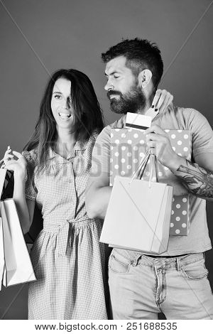 Guy With Beard And Girl With Smiling Faces Do Shopping. Man With Beard Holds Credit Card And Polka D