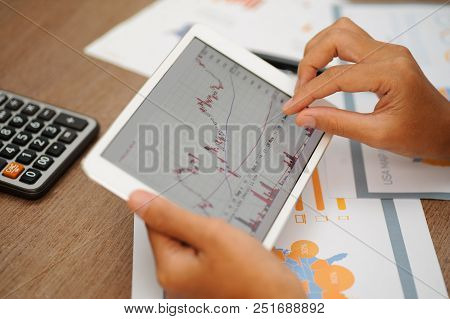 Closeup of trader working with candlestick chart and using tablet. Papers and calculator lying on desk. Trading and FOREX concept. Cropped view. poster