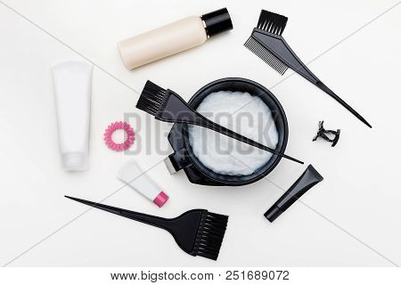 Tools for hair dye. brush, bowl and hair dye in tubes top view poster