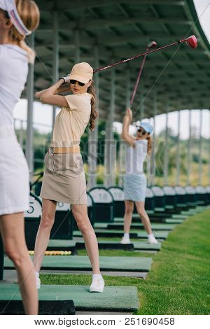Selective Focus Of Female Golf Player With Golf Clubs Playing Golf At Golf Course