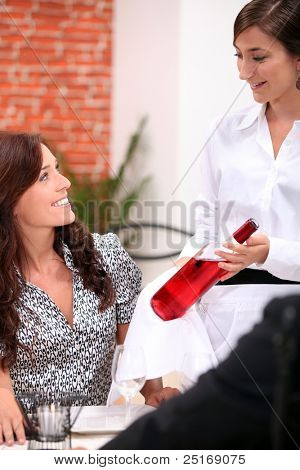 wine waitress and a customer in a restaurant