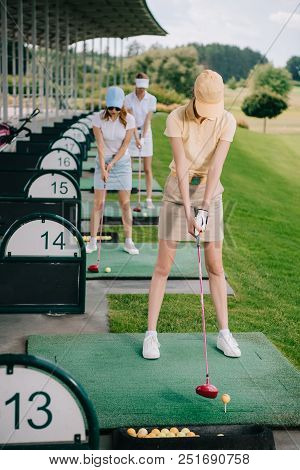 Selective Focus Of Women In Caps With Golf Clubs Playing Golf At Golf Course