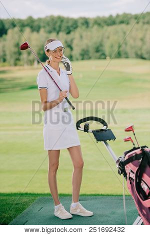 Smiling Female Golf Player In Polo And Cap With Golf Club In Hand Talking On Smartphone At Golf Cour