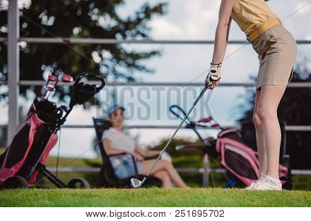Partial View Of Female Golf Player Playing Golf While Friend Resting Behind At Golf Course