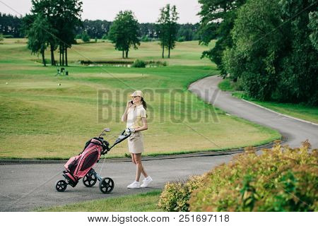 Side View Of Female Golf Player With Golf Gear Talking On Smartphone While Walking On Golf Course