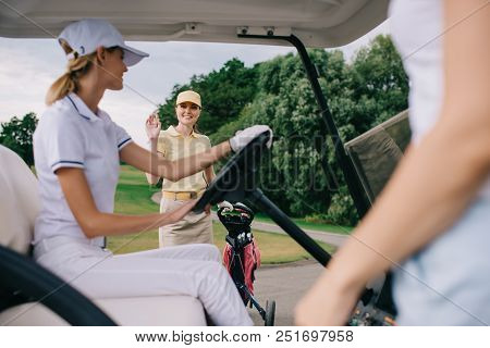 Smiling Female Golf Player Greeting Friend In Golf Cart At Golf Course