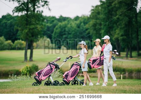 Side View Of Female Golf Players In Caps With Golf Equipment On Golf Course