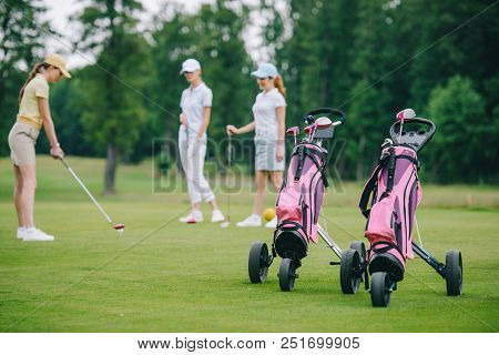 Selective Focus Of Golf Gear, Woman In Cap Playing Golf And Friends Standing Near By At Golf Course