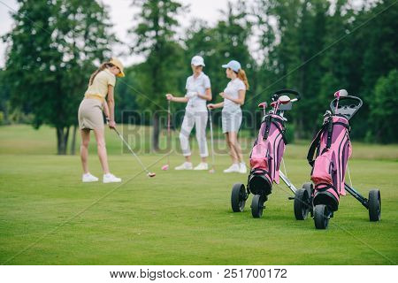 Selective Focus Of Golf Gear, Woman In Cap With Golf Club And Friends Standing Near By At Golf Cours