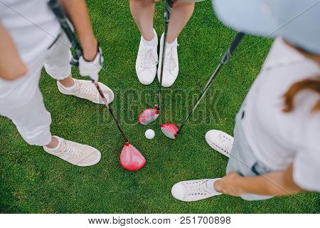 Overhead View Of Female Golf Players With Golf Clubs Standing On Green Lawn With Golf Ball In Middle