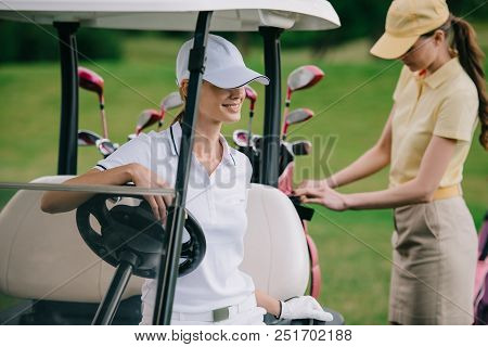 Selective Focus Of Female Golf Players In Caps At Golf Cart On Golf Course